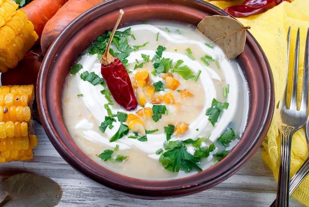 Soupe de maïs dans une assiette en céramique et ingrédients