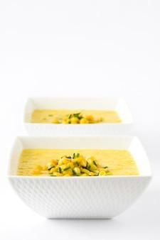 Soupe de maïs dans un bol blanc isolé sur blanc