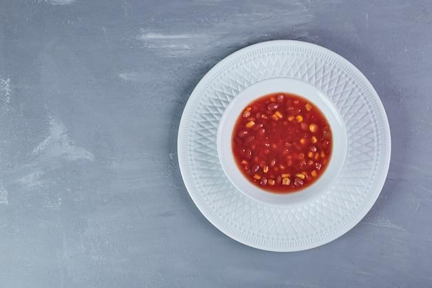 Soupe de maïs à la sauce tomate dans une assiette blanche.