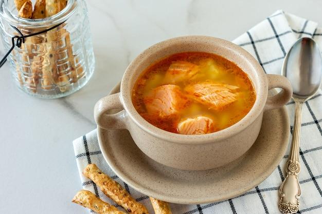 Soupe maison au saumon avec des bâtonnets de pain sur marbre