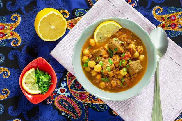 Soupe marocaine aux lentilles harira avec viande, pois chiches, tomate et épices. copieux, parfumé. se préparer pour l'iftar pendant le mois sacré du ramadan.