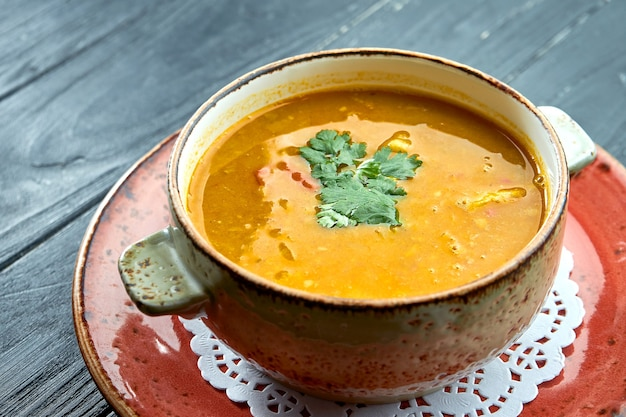 Soupe marocaine traditionnelle - harira, soupe de lentilles jaunes à la coriandre dans une assiette rouge sur une surface en bois noir. soupe diététique
