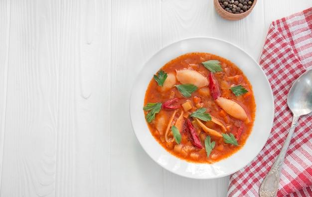 Soupe minestrone aux pâtes et aux herbes. cuisine italienne. plat végétarien. table à dinner. fond en bois blanc. copiez l'espace.