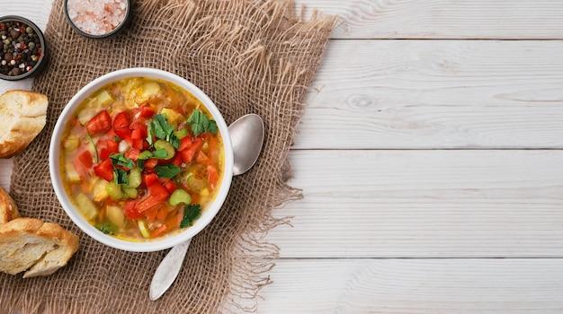 Soupe minestrone dans un plat blanc sur table en bois blanc