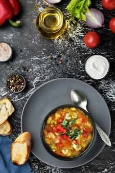 Soupe minestrone dans un plat noir sur une table sombre
