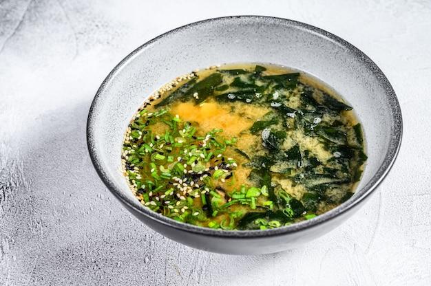 Soupe miso chaude dans un bol. fond blanc. vue de dessus
