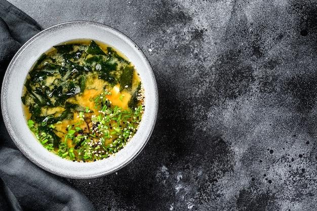 Soupe miso chaude dans un bol. fond noir. vue de dessus. espace copie