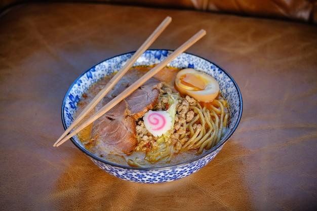 Soupe de nouilles asiatique avec des baguettes dans un bol
