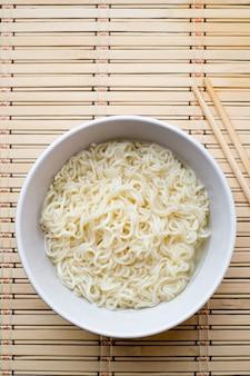 Soupe de nouilles asiatique dans un bol avec des baguettes en bois sur une vue de dessus de tapis de bambou copyspace