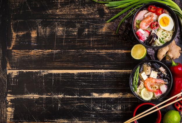 Soupe de nouilles asiatiques dans un bol noir avec des baguettes sur un fond en bois texturé foncé.