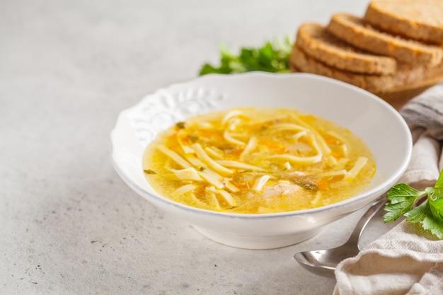 Soupe de nouilles au poulet fait maison dans une assiette blanche, espace copie.