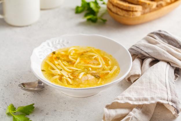 Soupe de nouilles au poulet fait maison dans une assiette blanche, fond blanc.