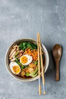 Soupe de nouilles ramen de style asiatique avec bok choy, carotte, citron vert, graines de sésame, poulet et œuf
