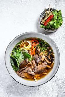 Soupe de nouilles de riz frais vietnamien pho bo avec boeuf, herbes et chili