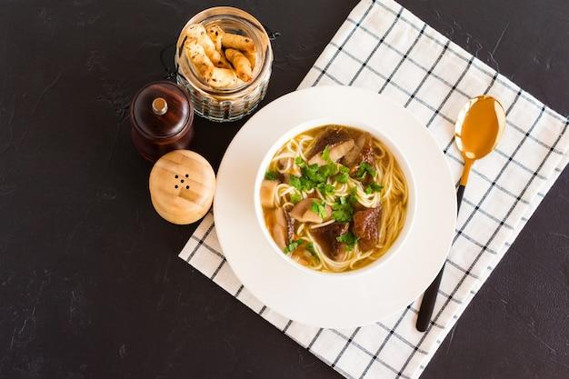 Soupe parfumée aux champignons dans une assiette creuse blanche, avec une cuillère dorée sur une serviette en tissu. vue de dessus. fond noir.