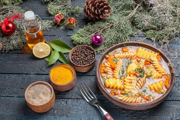 Soupe de pâtes délicieuse vue à mi-hauteur de pâtes italiennes en spirale avec des verts sur un bureau bleu foncé cuisine soupe de pâtes dîner plat couleur