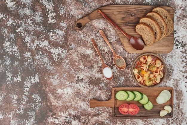 Soupe de pâtes avec salade de légumes et pain.