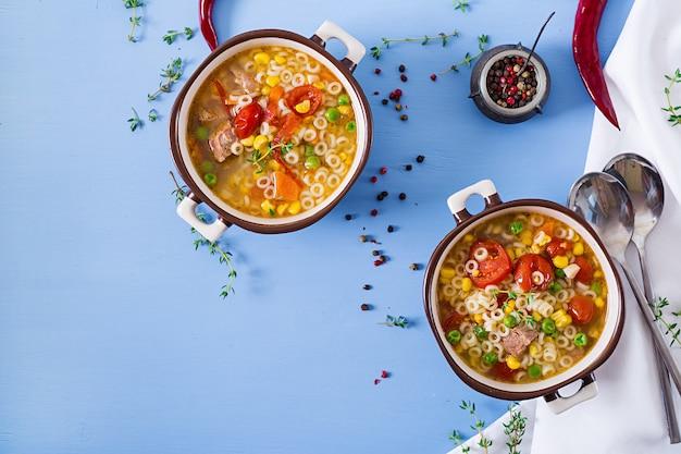 Soupe avec des petites pâtes, des légumes et des morceaux de viande dans un bol sur la table bleue. nourriture italienne.