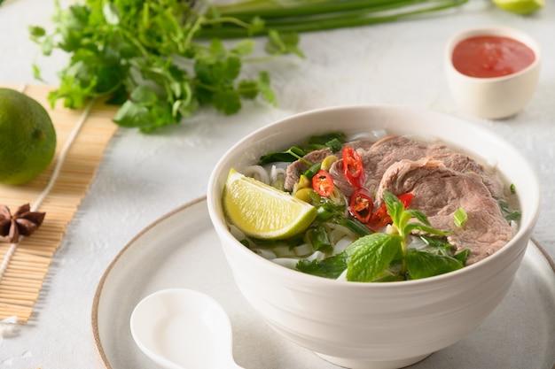 Soupe pho bo au boeuf dans un bol blanc sur fond clair cuisine vietnamienne