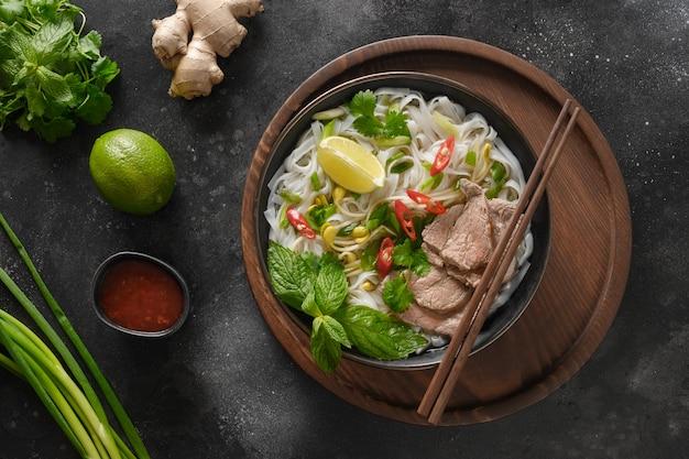Soupe pho bo au boeuf dans un bol sur fond noir cuisine vietnamienne