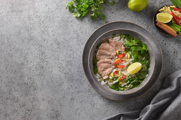 Soupe pho bo au boeuf dans un bol gris sur la cuisine vietnamienne grise