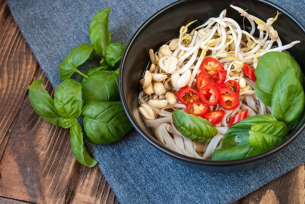 Soupe pho végétarienne à la vietnamienne avec garnitures et baguettes