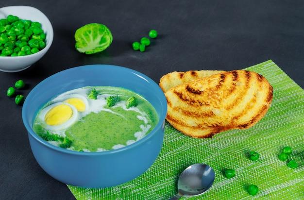 Soupe de pois verts et brocolis avec des croûtons sur fond en bois