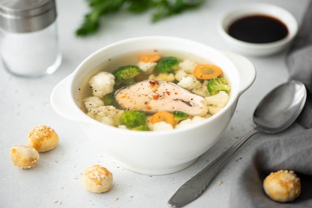 Soupe de poisson au saumon rose, chou-fleur et brocoli dans un bol blanc