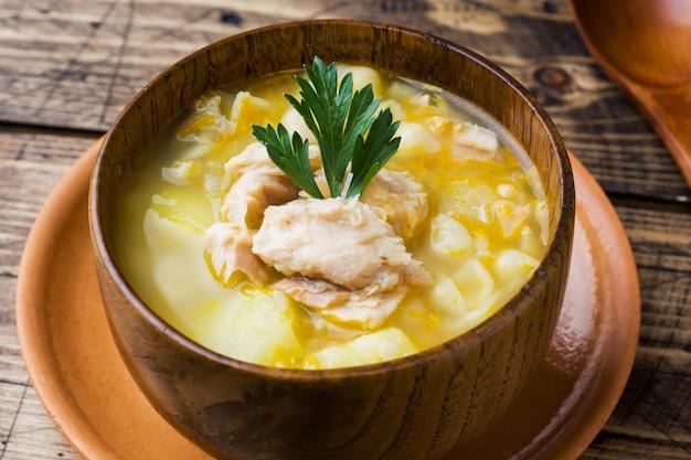 Soupe de poisson dans un bol en bois avec des herbes fraîches.
