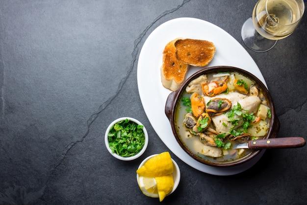 Soupe de poisson de fruits de mer dans des bols d'argile servie avec du vin blanc froid.