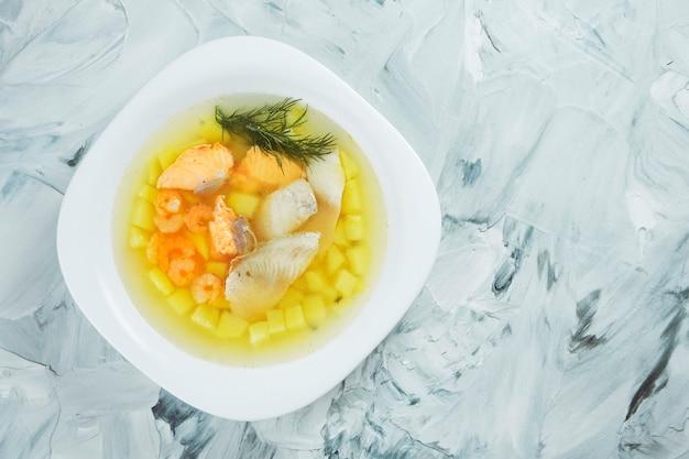 Soupe de poisson transparente maison avec bar, saumon et crevettes dans un bol blanc sur une table grise. fruit de mer