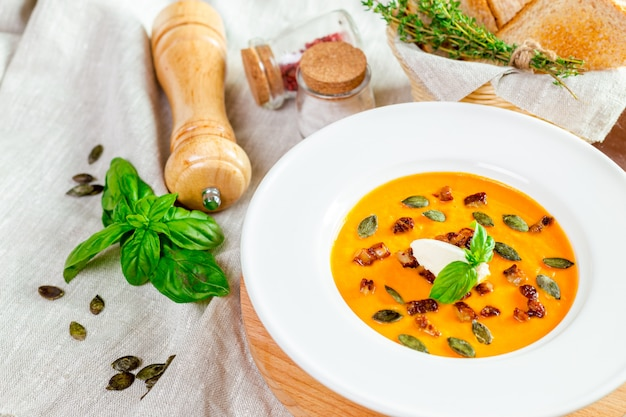 Soupe de potiron en assiette blanche