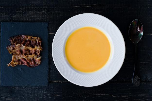 Soupe de potiron au bacon frit en assiette