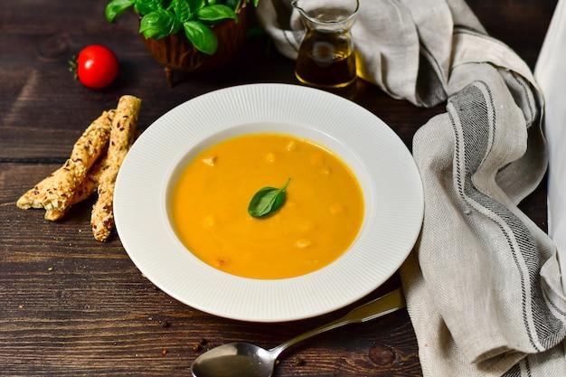 Soupe de potiron au basilic et de gressins dans une assiette en porcelaine blanche, recette de potiron