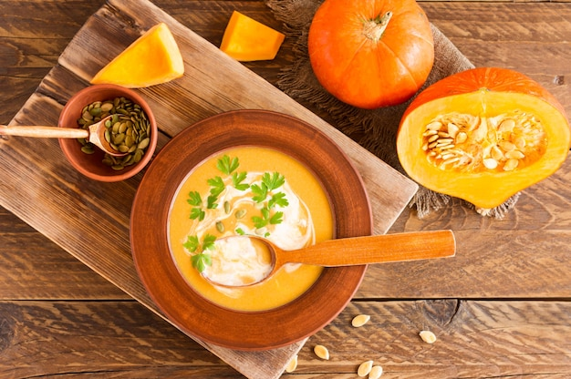 Soupe de potiron au lait de coco avec graines de potiron et persil. nourriture diététique. fond en bois. style rustique.