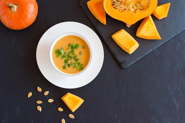 Soupe de potiron d'automne au lait de coco et au persil dans une assiette creuse. ardoise avec citrouille mûre hachée.