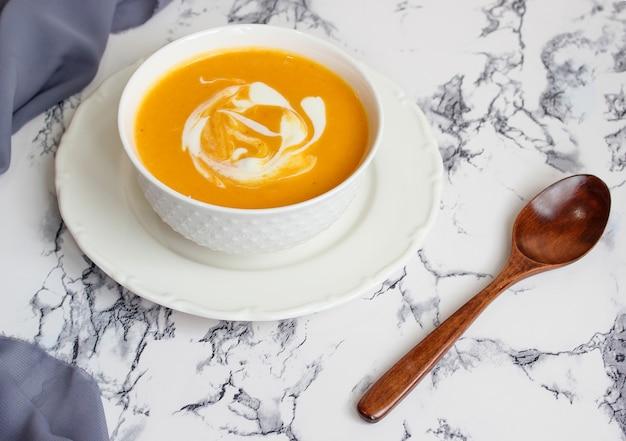 Soupe de potiron blanche avec tissu gris et tranches de courge musquée