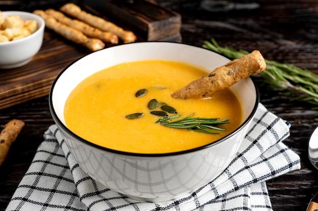 Soupe de potiron et carotte à la crème, graines de citrouille, croûtons et bâtonnets de pain grossini sur fond en bois de dar k. style rustique, mise au point sélective.