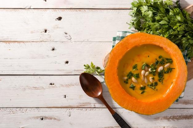 Soupe de potiron et carotte sur une table en bois blanche.