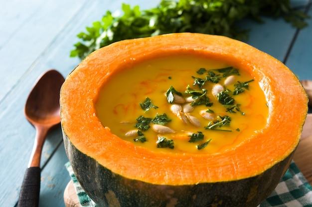 Soupe de potiron et carotte sur une table en bois bleue.