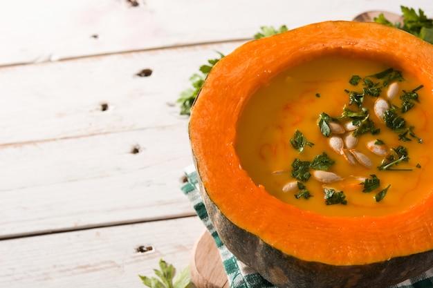 Soupe de potiron et carotte sur une table en bois.