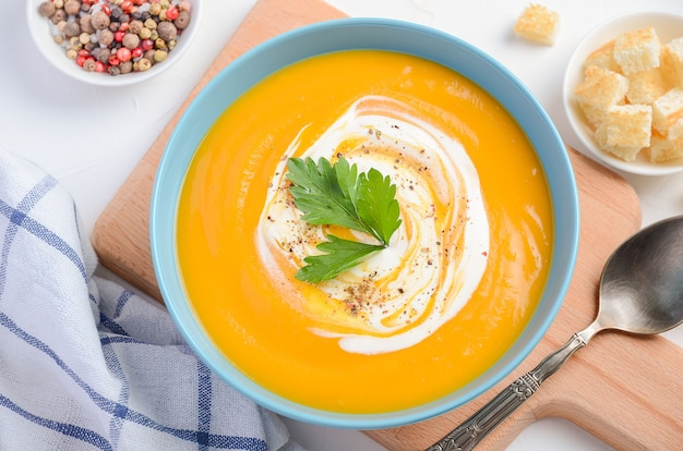 Soupe de potiron à la crème et au persil sur fond blanc.
