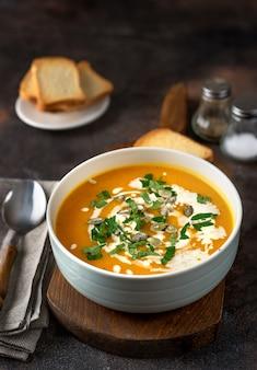 Soupe de potiron à la crème et au persil sur une table sombre et rustique