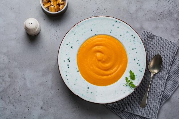 Soupe de potiron à la crème, des morceaux de pain et des noix de cèdre dans une plaque en céramique grise sur la surface de la table grise