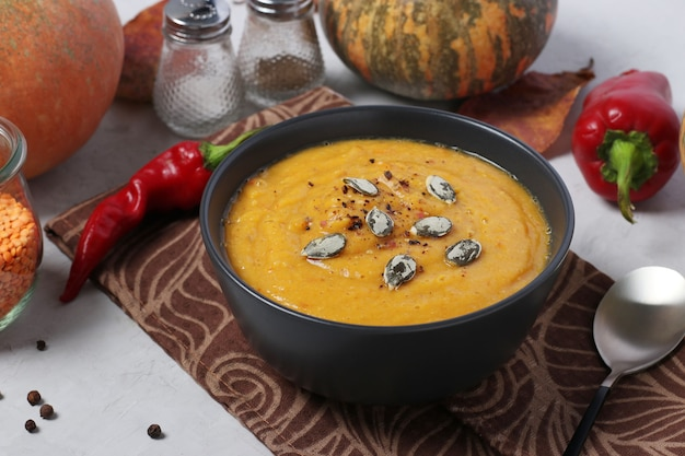 Soupe de potiron crémeuse d'automne végétarienne aux lentilles rouges sur assiette sombre. fermer. format horizontal.