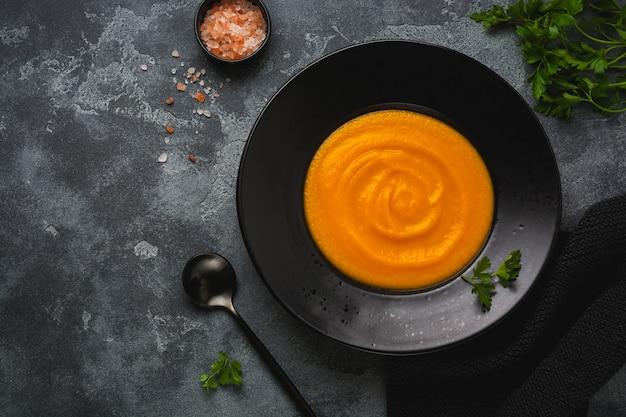 Soupe de potiron dans une assiette en céramique noire sur une surface en bois sombre