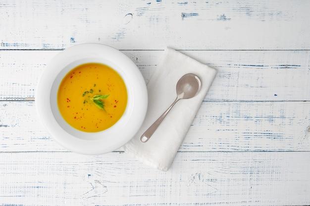 Soupe de potiron dans une assiette kénamique blanche sur une table en bois.