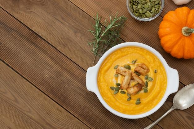 Soupe de potiron dans un bol avec des graines de potiron fraîches. aliments d'automne.