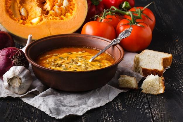 Soupe de potiron dans un bol sur une table rustique avec du pain