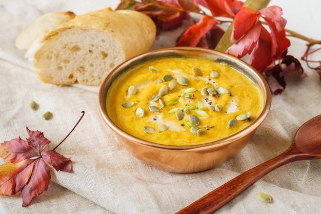 Soupe de potiron dans un pot en cuivre servi avec des graines et de la crème